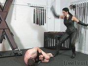 Leather mistress torturing male prisoner