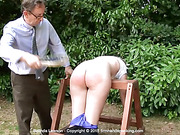 Bare bottom slippering for Belinda Lawson, lying over a
