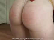 Alison bends over a desk